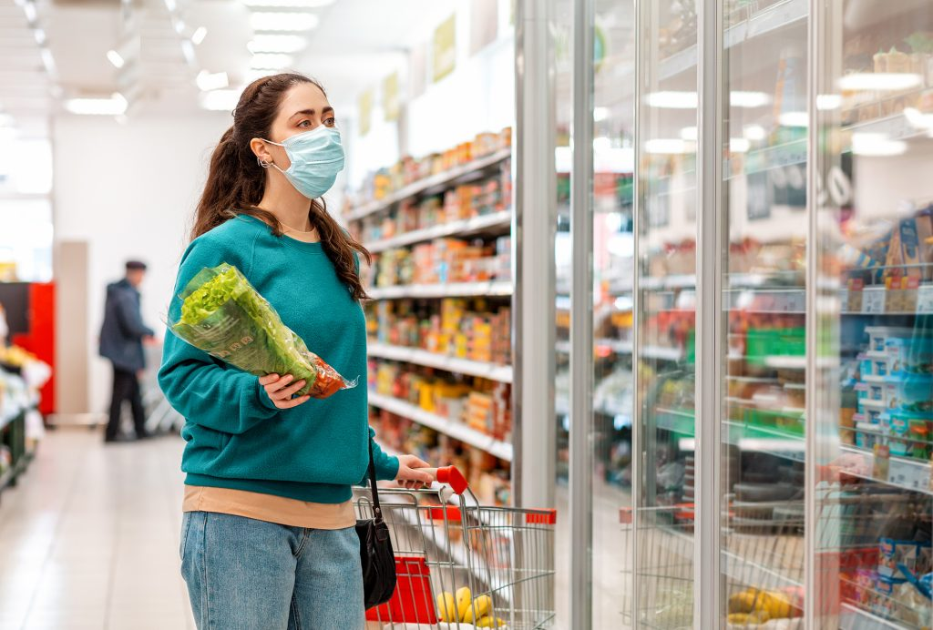 Woman shopping at a grocery store during covid-19