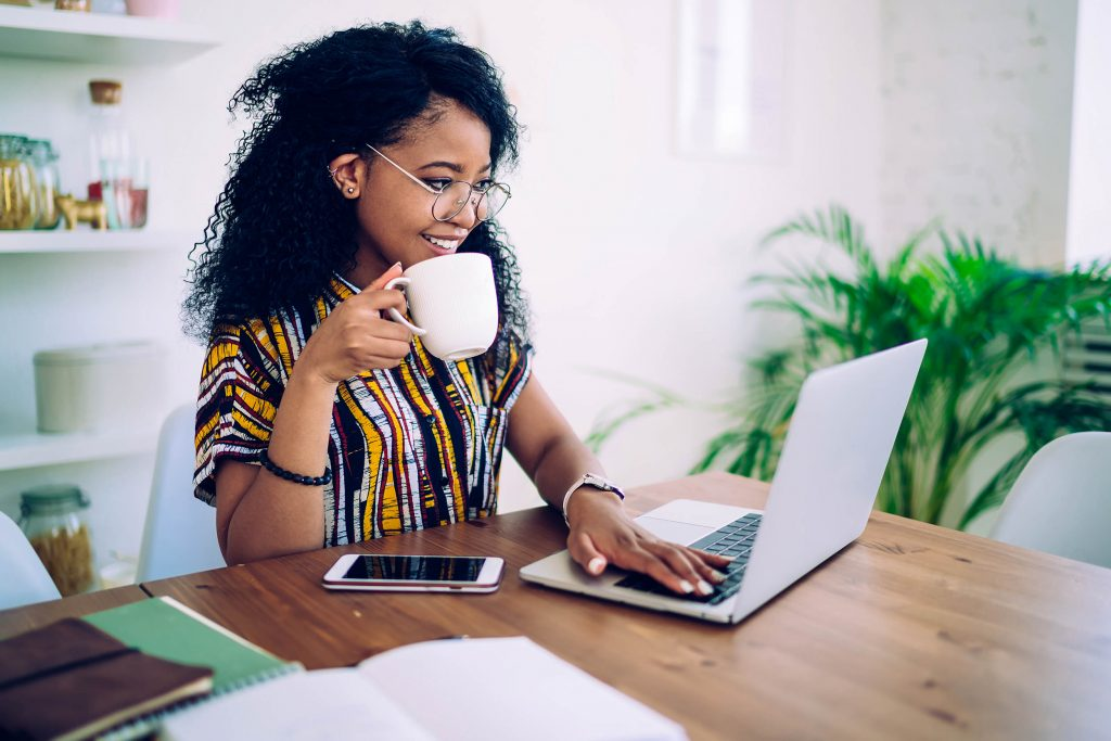 Woman drinking coffee while working
