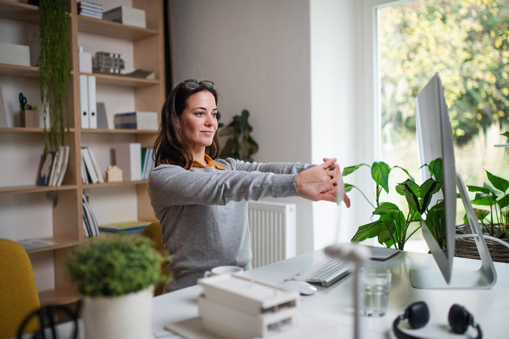 woman stretching while working from home